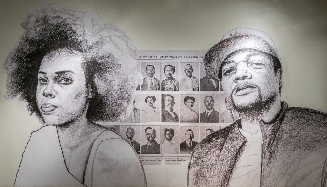Large-scales sketches of a dark-skinned man and woman are wheatpasted onto a wall in front of a newspaper page featuring photos of dark-skinned men and women