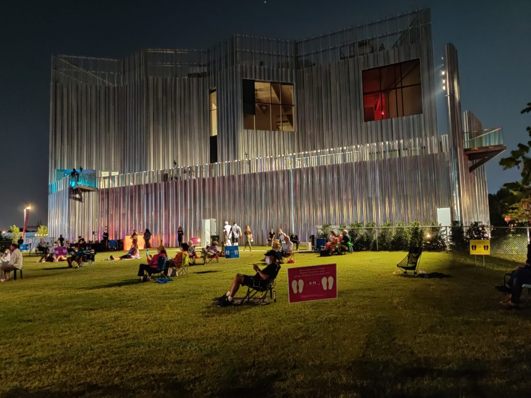 A socially distanced crowd enjoys a concert on a green lawn in front of a metal building in the evening
