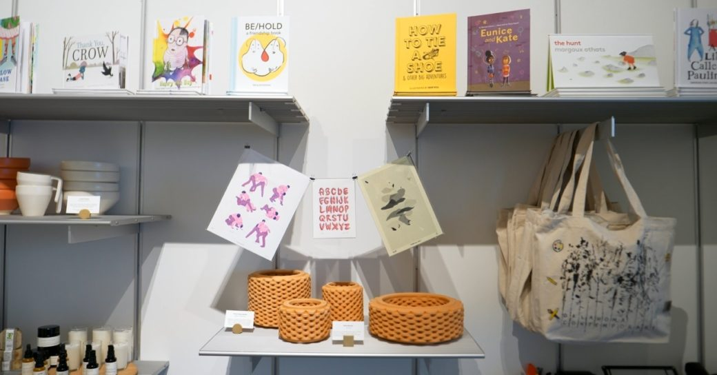 A wall featuring shelved and hanging items for sale, ranging from a hand-printed tote bag to colorful art prints, books and more