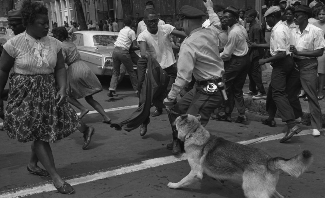 In this black and white photograph, a police officer with a dog gestures toward a crowd of Black people, many fleeing, on a busy street