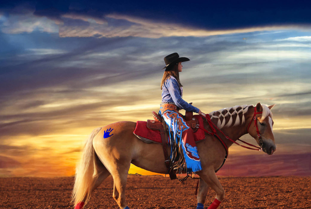A photograph in which a cowgirl in ornamented chaps rides a chestnut horse with a white mane across a colorful skyline