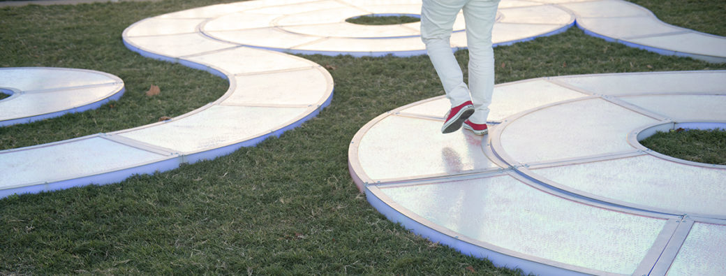 A detail photo depicts a pair of legs in white pants and red shoes, walking across the surface of a winding light sculpture