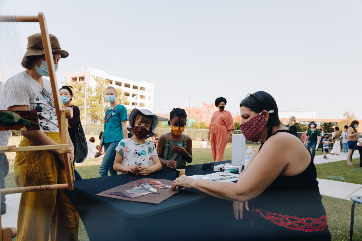 Adults and children wearing masks stand around a table working on an art project