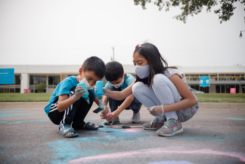 Three masked children create artwork on the pavement
