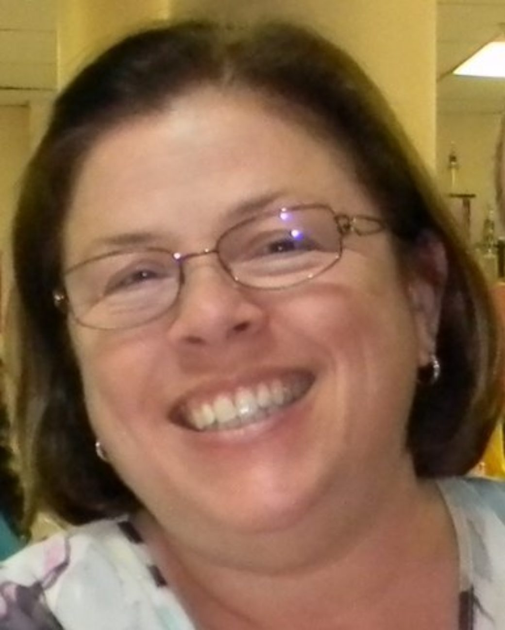 Color photo of a woman with short, brown hair wearing glasses smiles at the camera.