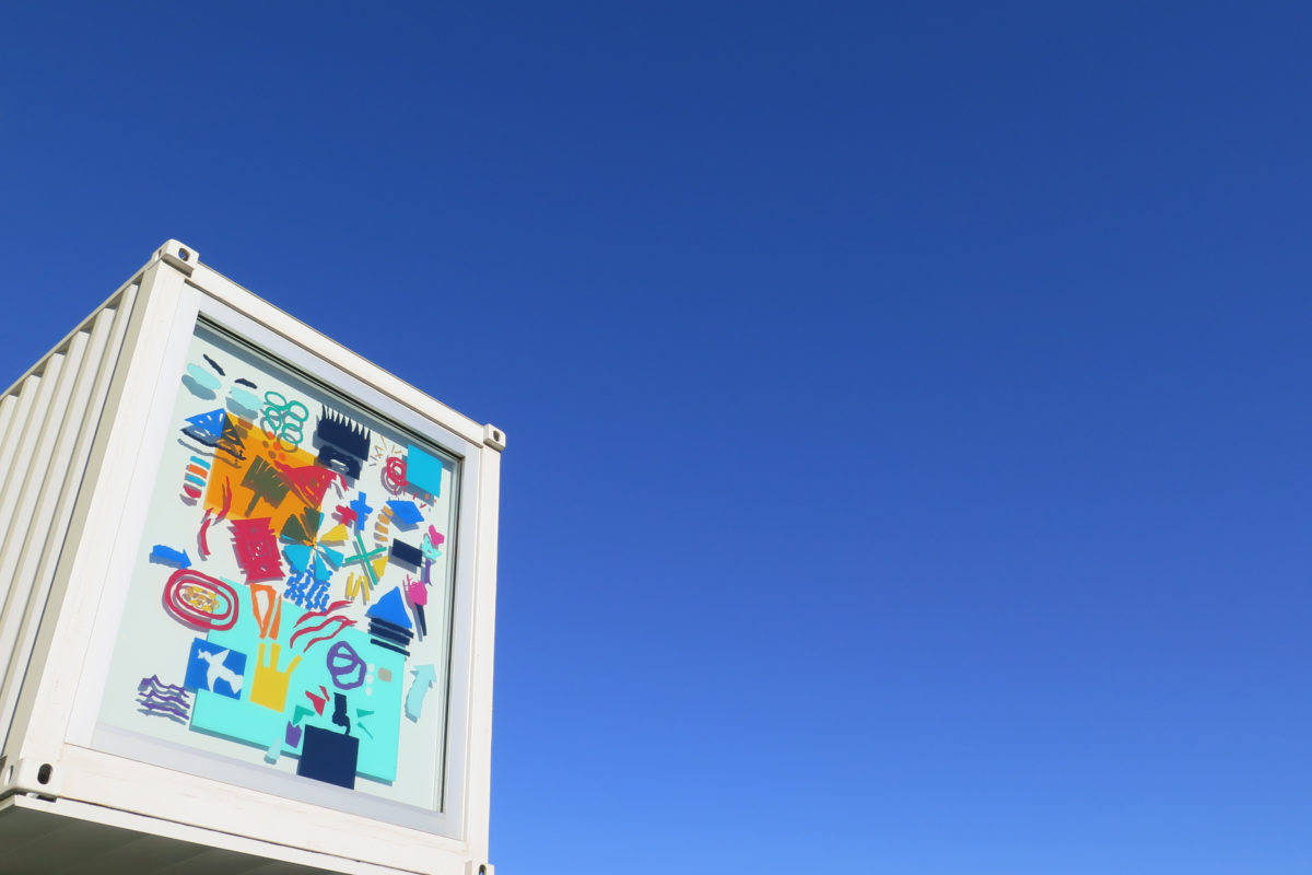 A window of a white shipping container building features a multicolored, hieroglyphic mural in vinyl