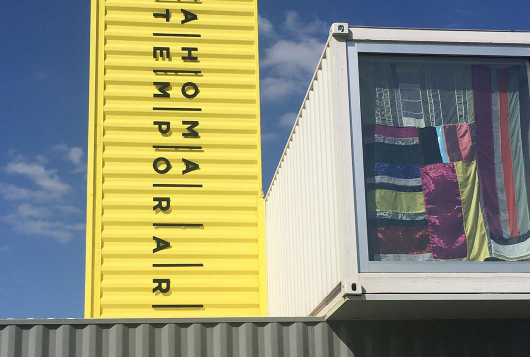 A closeup of a white and gray shipping container building with multicolored fabric hanging in the window