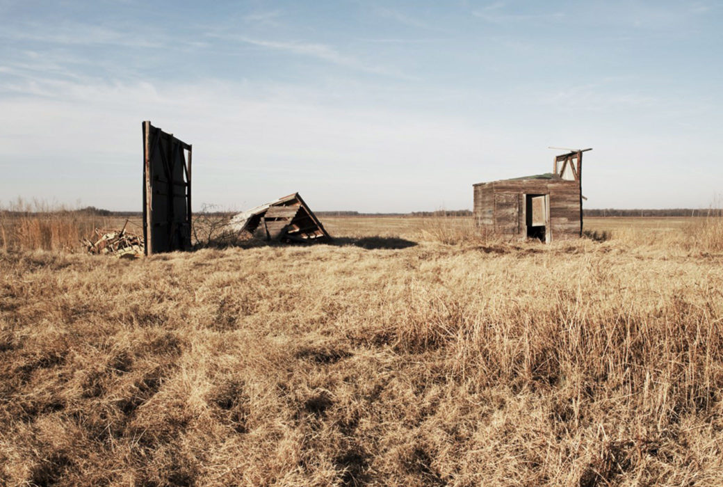 A photo of wooden buildings in various states of collapse in an  empty field