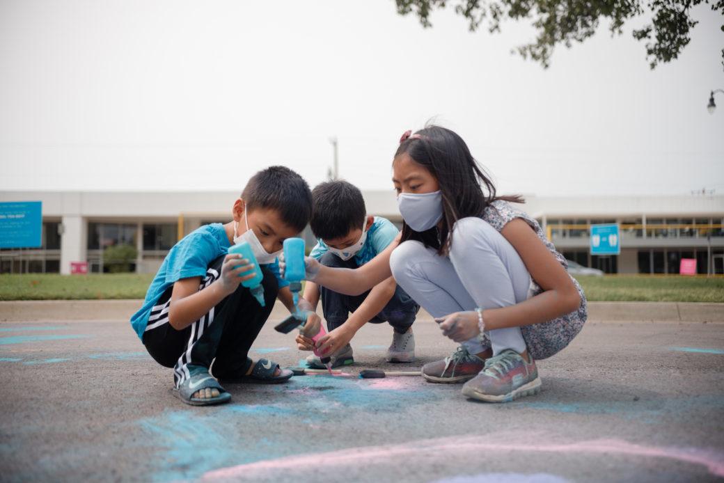 Three masked children create artwork on the pavement