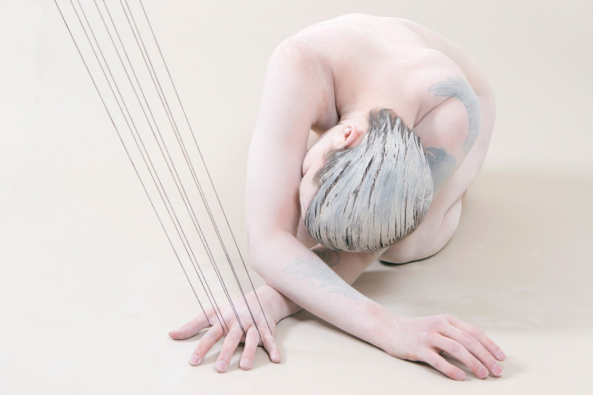A nude figure with short hair coated in clay kneels on the floor with arms crossed and fingers woven into threads rising from the fame