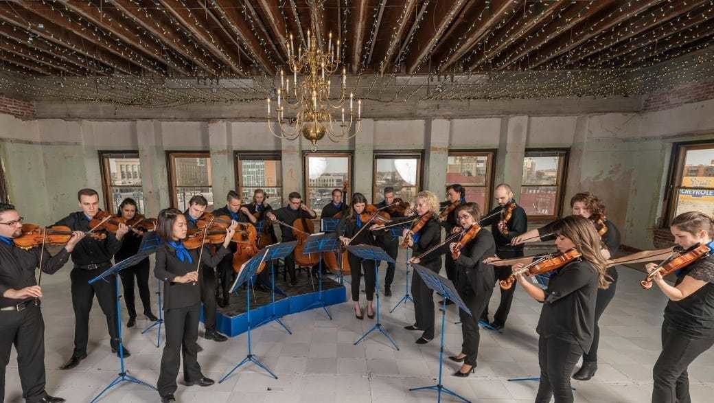 A chamber orchestra performs under a chandelier
