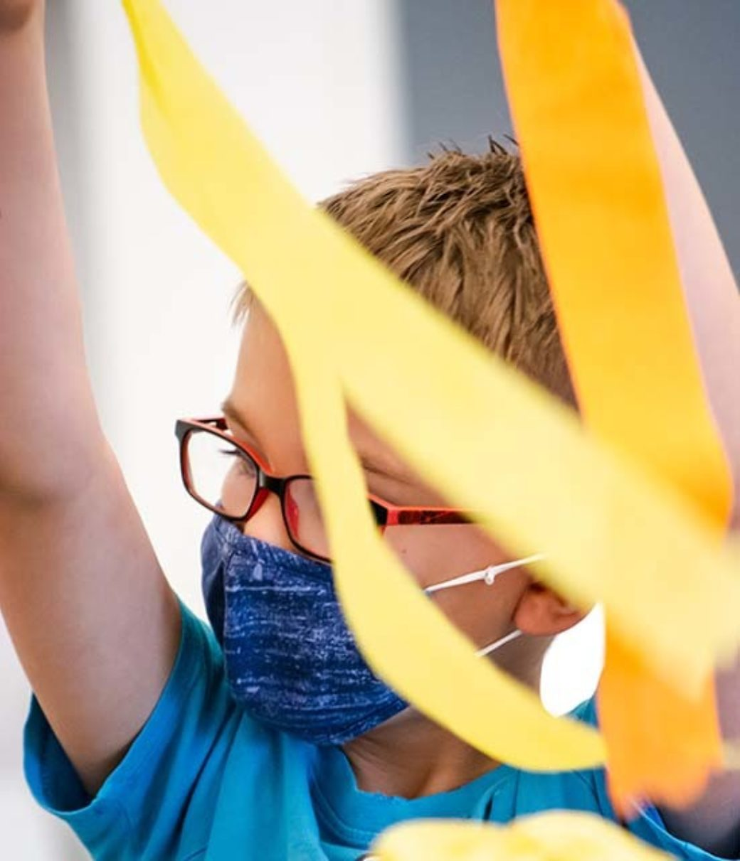 A child with glasses plays with crepe paper streamers
