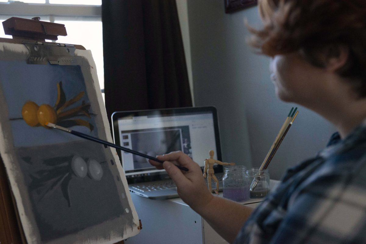 A person holds a brush up to a small painting of tangerines with a computer in the background