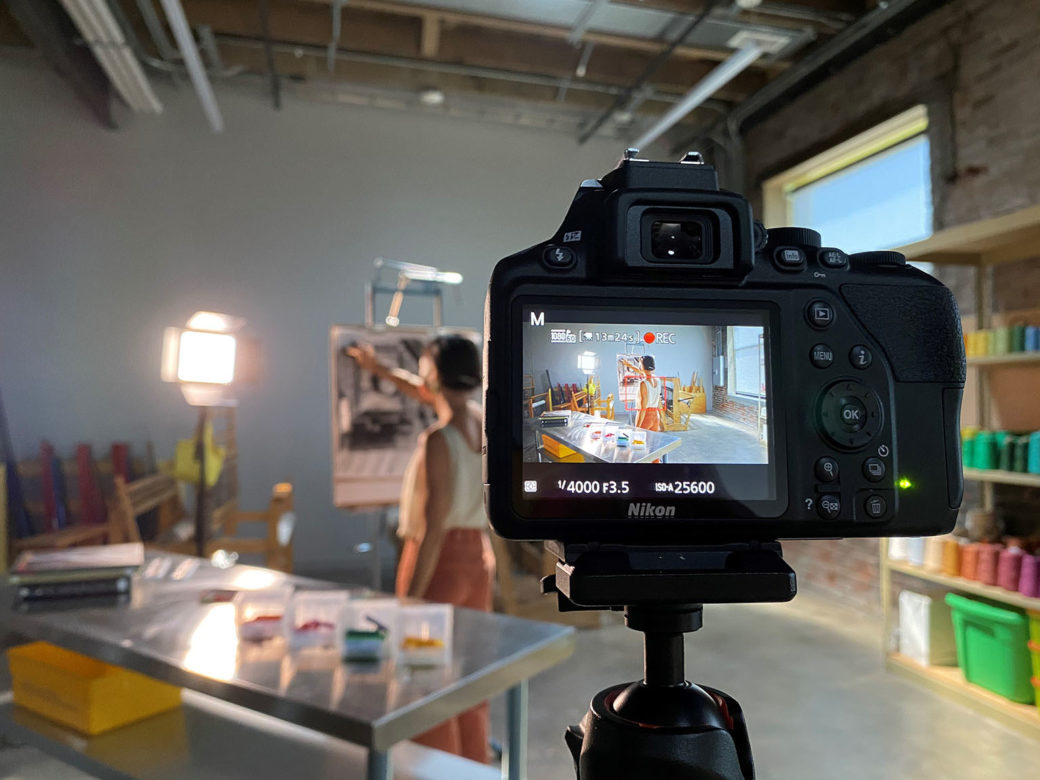 A photo depicts a video camera capturing an artist as they work on an easel