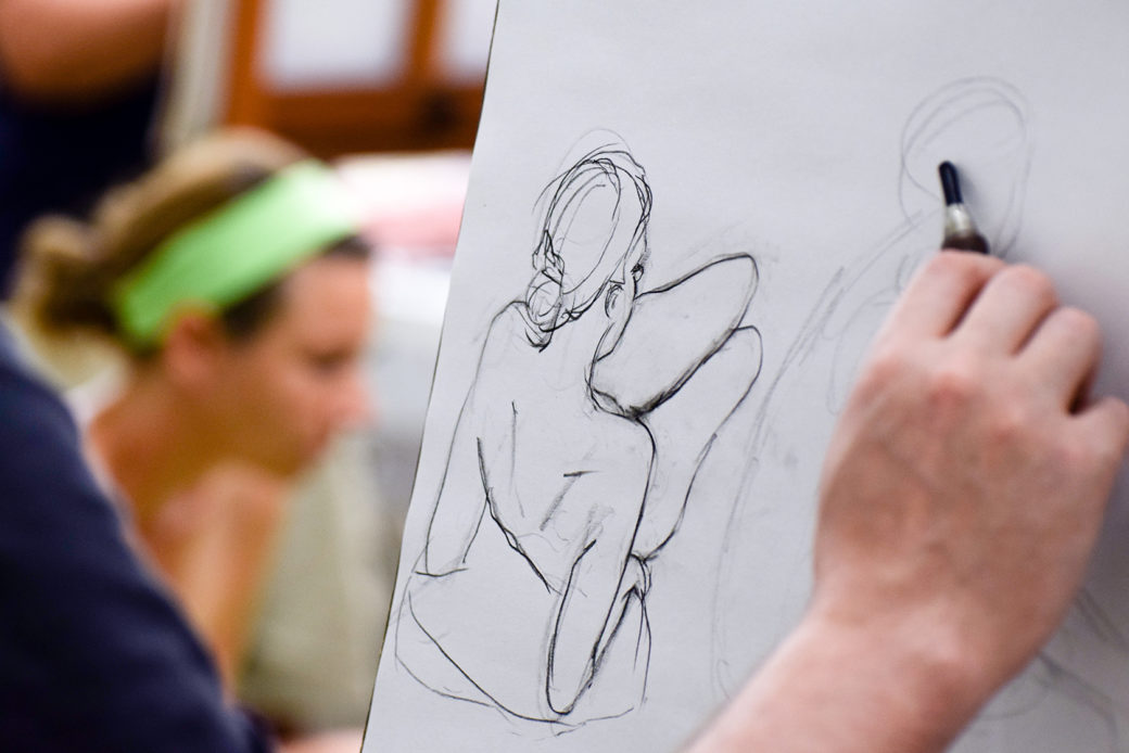 A hand drawing a figure on a pad with person out of focus in background