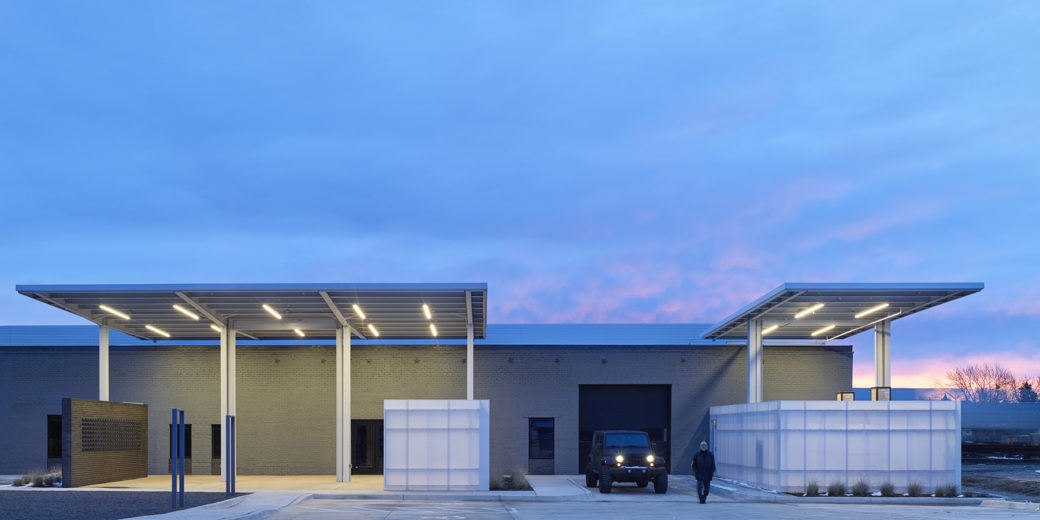 A Jeep is parked in front of a small gray building while the sun sets behind it