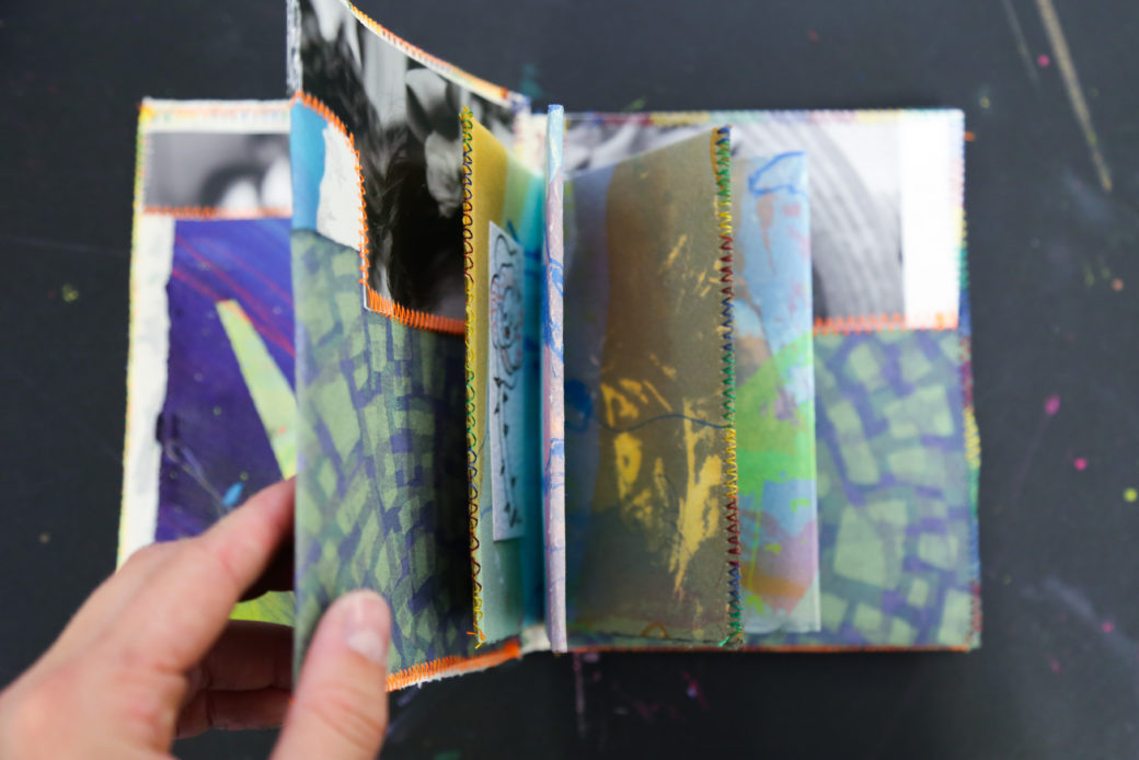 A hand flips through a colorful, handmade book featuring abstract art