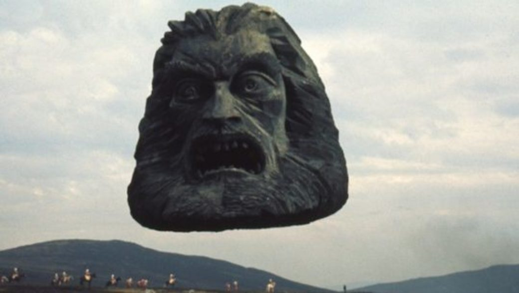 A fantastical image of a floating head carved from stone, with a mountain range in the distance