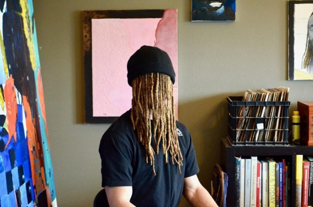 A figure sits in the middle of a room, wearing a black beanie, with dreadlocks completely obscuring their face