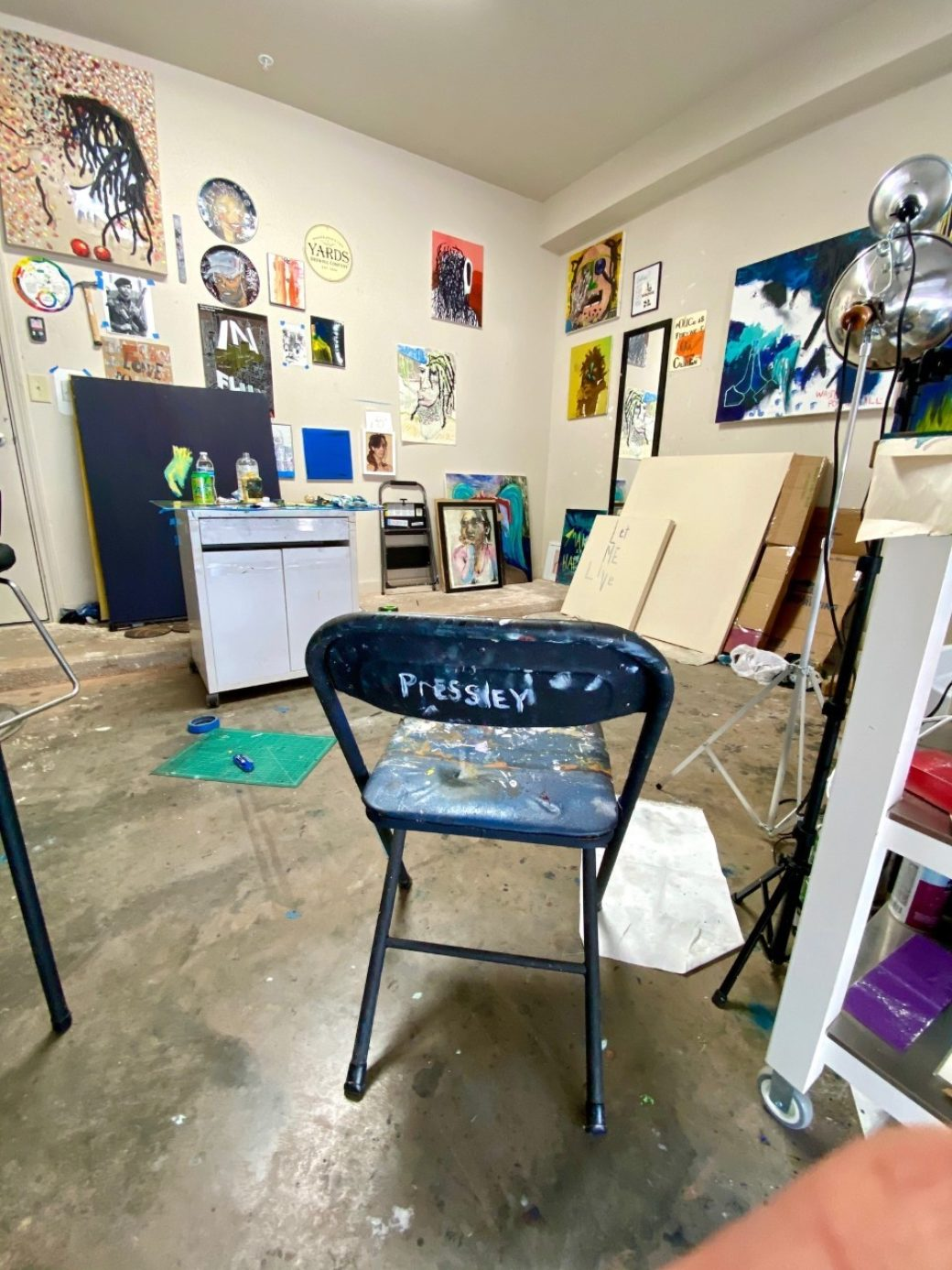 An empty studio featuring vibrant paintings and a metal chair with Pressley written on the back
