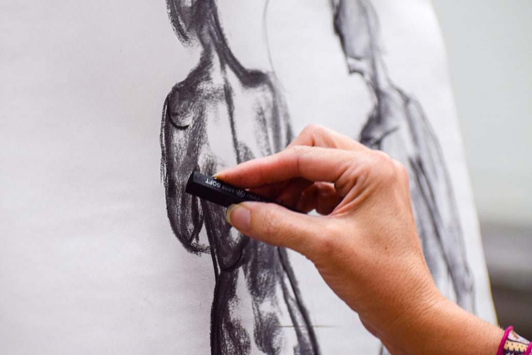A tightly cropped photo of a hand working on a human figure in charcoal