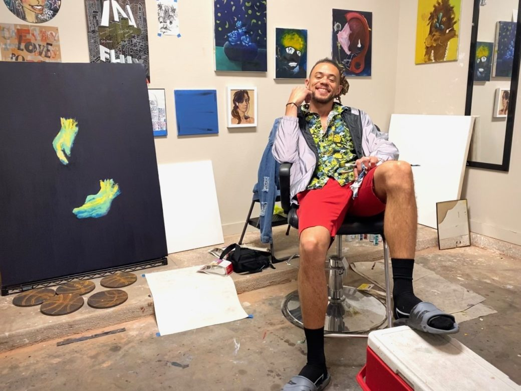 A person in red shorts and black socks sits in a studio, surrounded by paintings