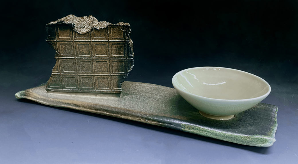 A ceramic sculpture featuring a fragment of a wall and a bowl set on on a rectangular base