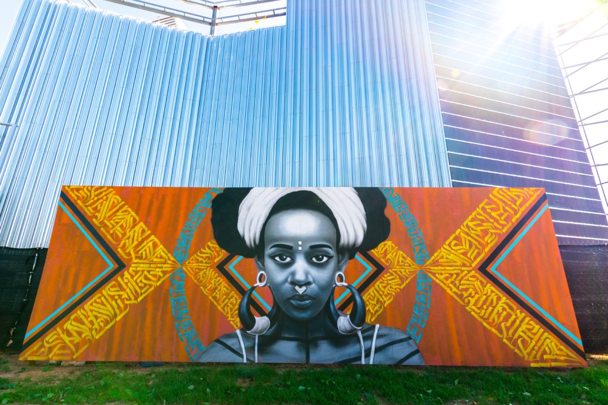 A large mural of a dark-skinned woman in traditional adornments is painted on plywood in front of a construction fence