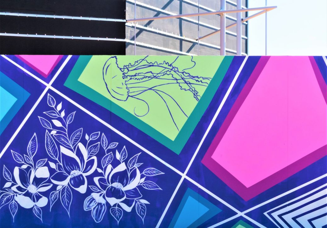A large mural of pink, blue and white geometric shapes with flowers and jellyfish inside the shapes stands in front of a building under construction