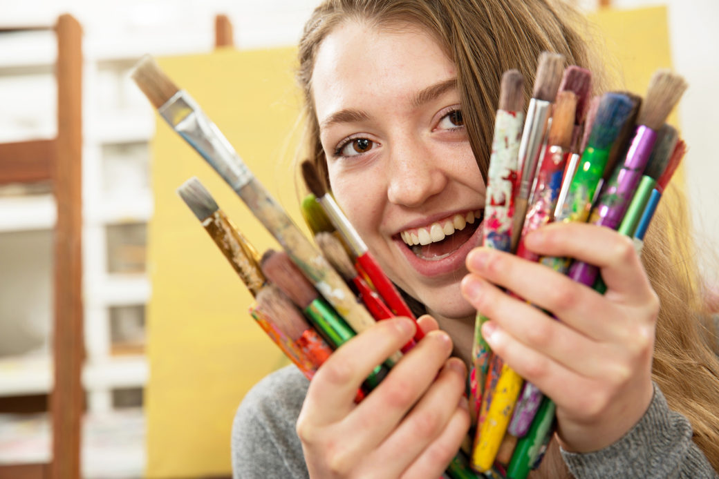 A smiling teen holds an array of paint brushes