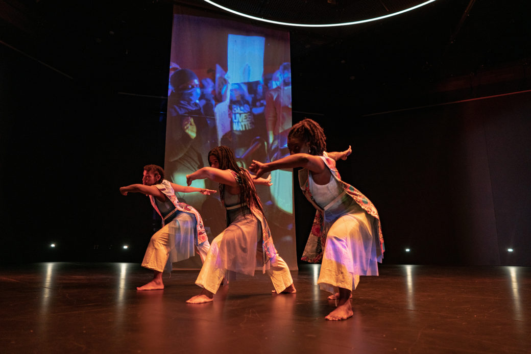 Three figures dance on stage against projected photography