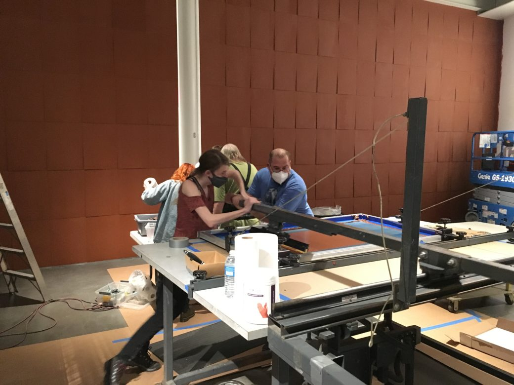 """A team works at a screenprinter in a room with brown """"shingled"""" walls"""