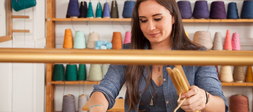 An adult working behind a loom stands in front of a wall full of colorful yarn
