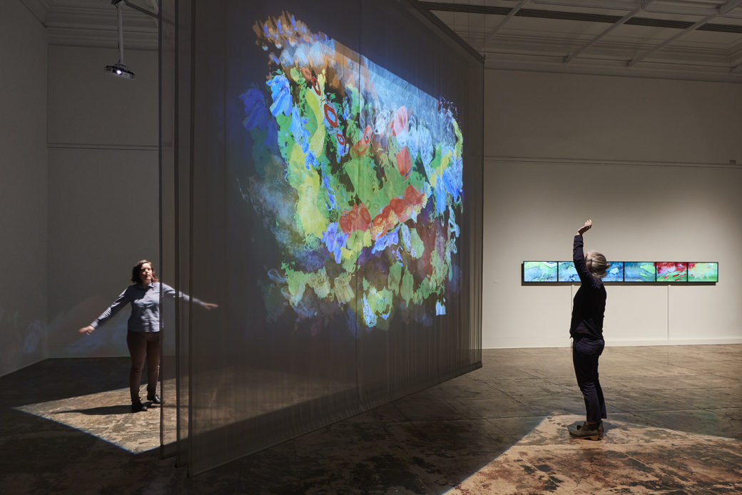 An installation using three large fabric scrims hangs in a gallery with, abstract images projecting on the fabric as two adults interact with the piece