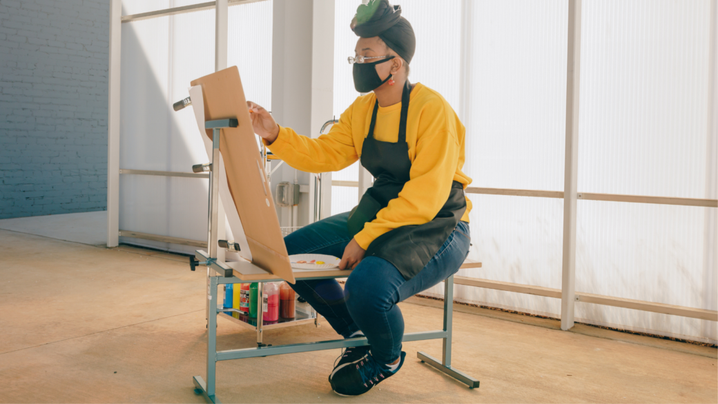 Woman wearing a yellow shirt sitting on an easel bench and painting outdoors