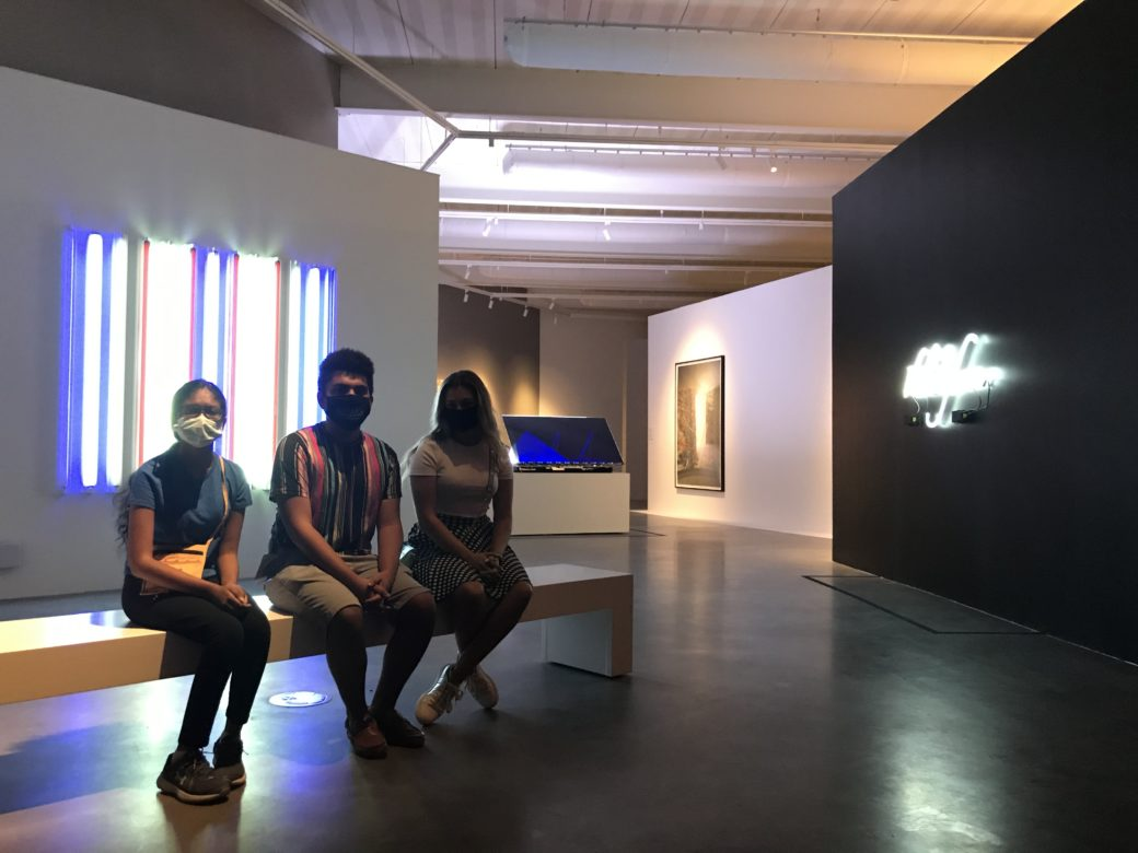 Three young people wearing face masks sit on a bench in an art gallery featuring light sculptures in the background
