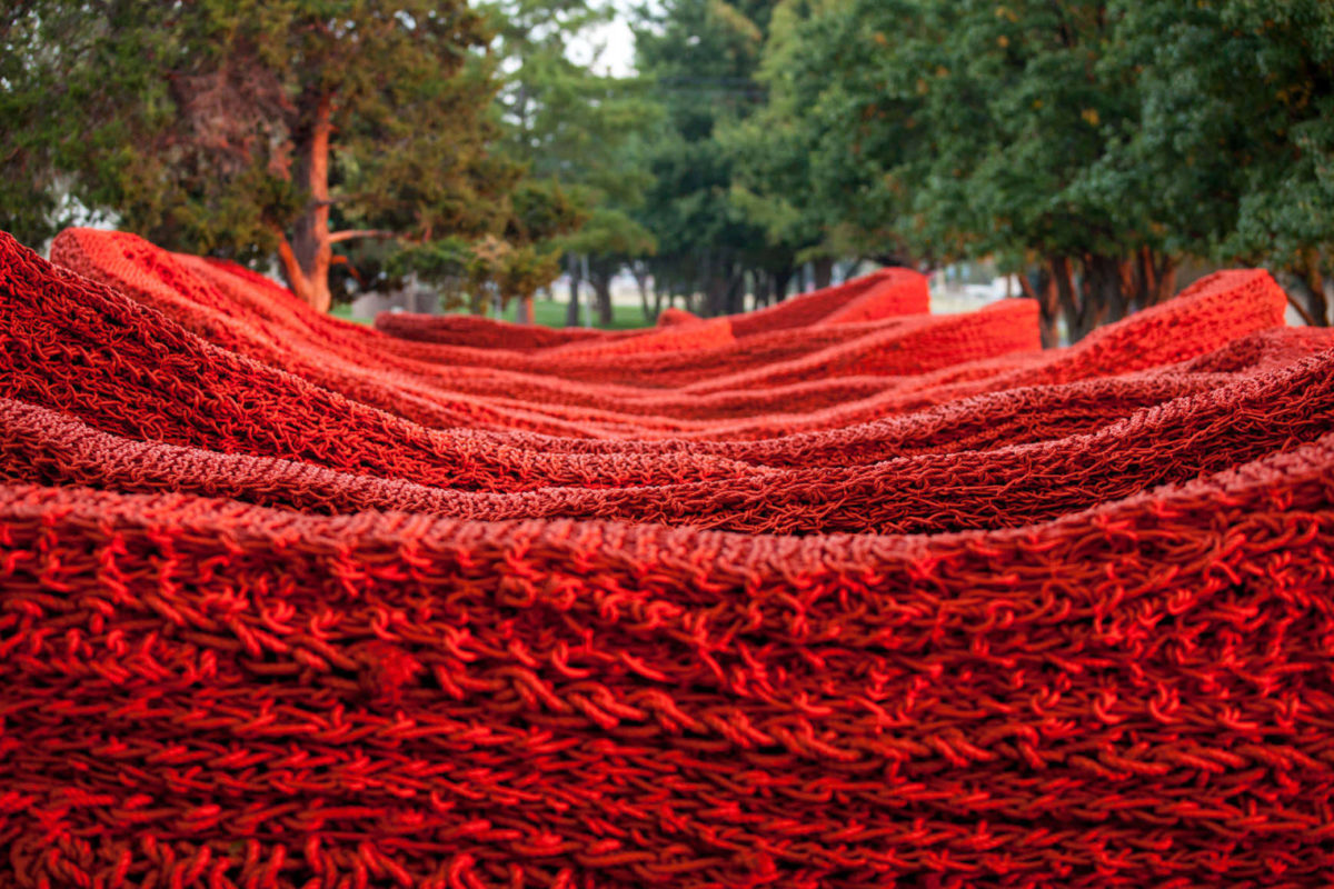 Red knit structure weaves left to right through a clearing of trees