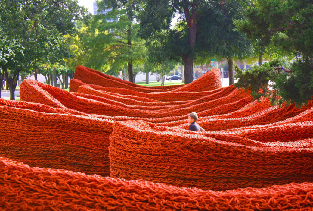 A child runs through a a large, winding sculpture made of red rope
