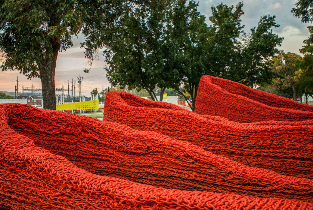 The curved walls of a large, red rope sculpture among trees with city buildings in the background