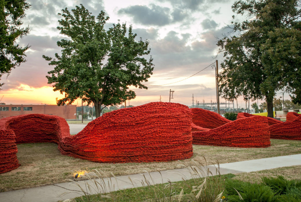 A side view of a large red rope sculpture shows the winding caverns and curves
