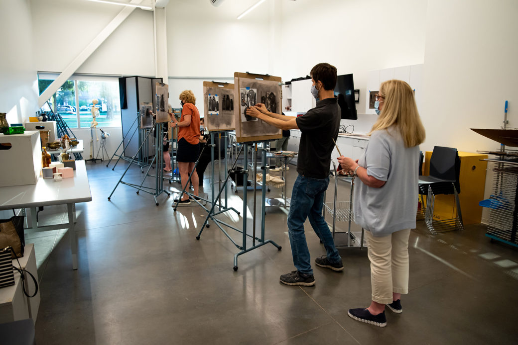 An instructor observes an artist working in a busy studio
