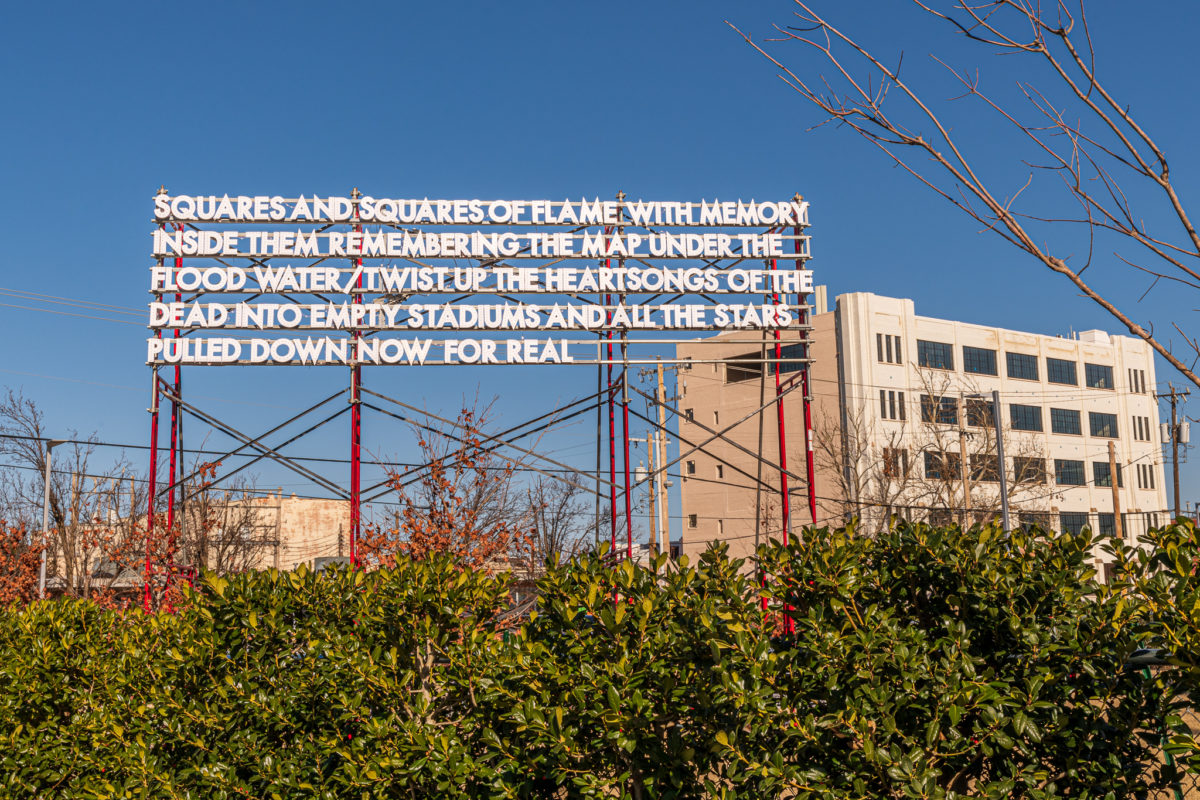 A billboard-size poem in LED light stands on scaffolding behind a row of bushes in front of a blue sky.