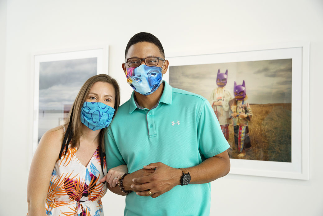 Two adults in masks stand in front of photographs in a gallery