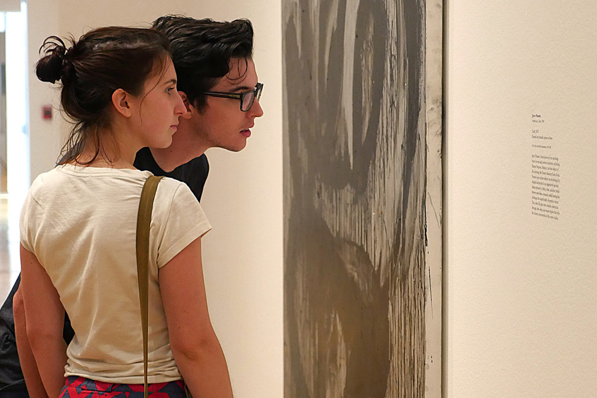Two people gaze at a black and white canvas