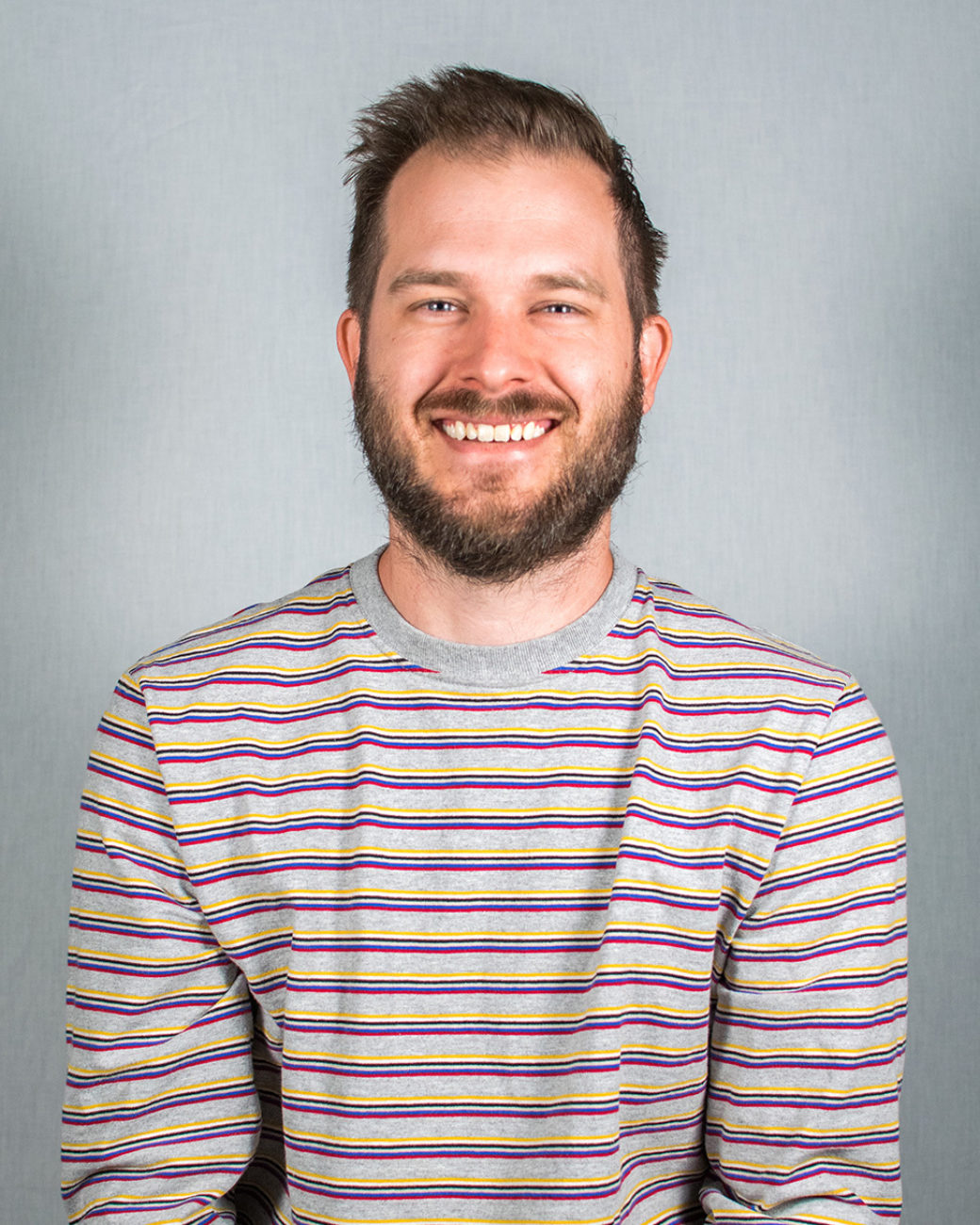 A headshot of adult person with a beard wearing a striped shirt