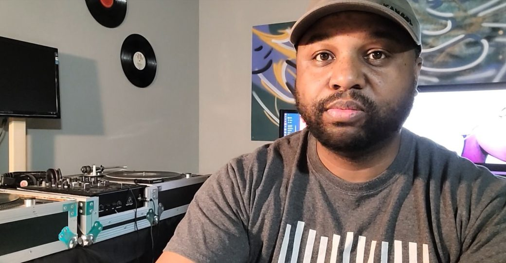 DJ wearing ballcap and gray shirt with turntables and vinyl records in background