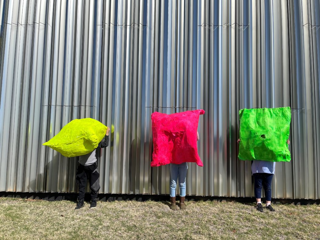 Three kids hold colorful paper mache sculptures in front of their bodies outside a silver building