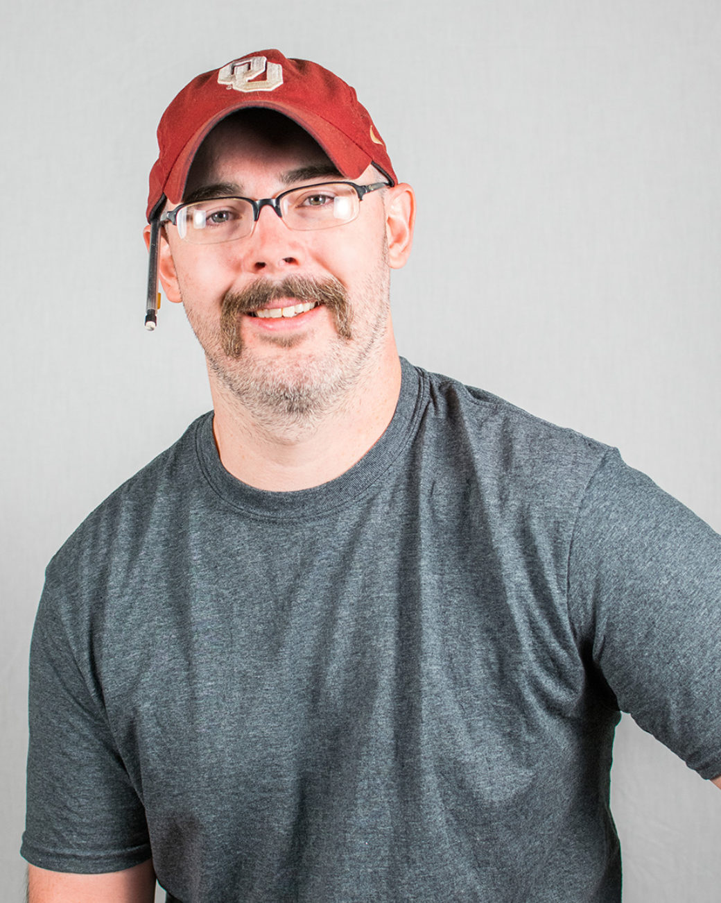 An adult wears a gray shirt and red hat with a pencil in it