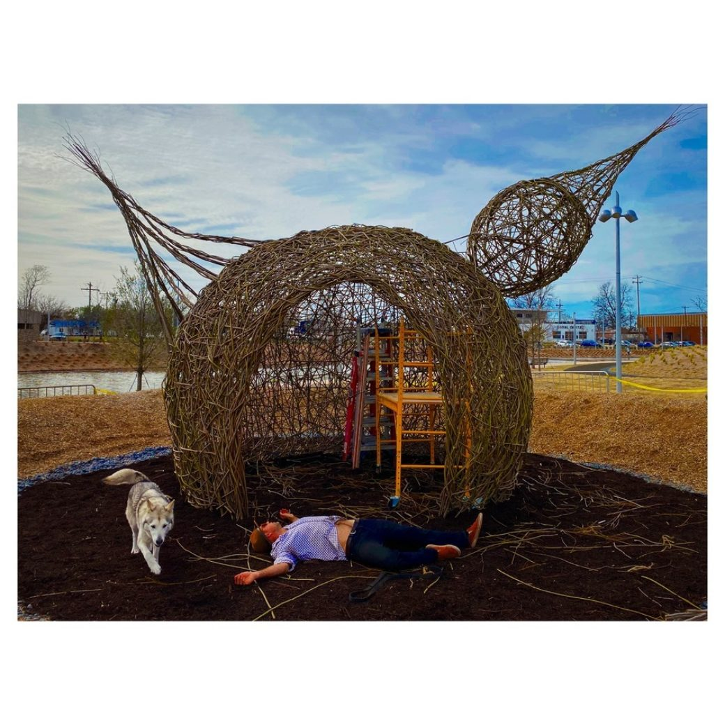 A person lies on the ground in front of a woven stick hut sculpture in the shape of a bird, with a white dog walking in the frame