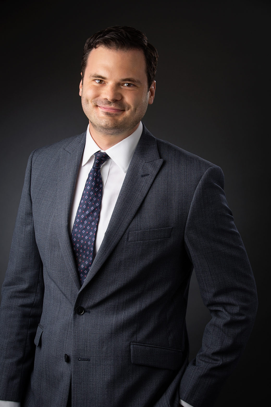 An adult male wearing a suit smiles